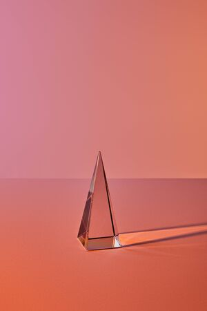 crystal transparent pyramid with light reflection on orange background Stockfoto