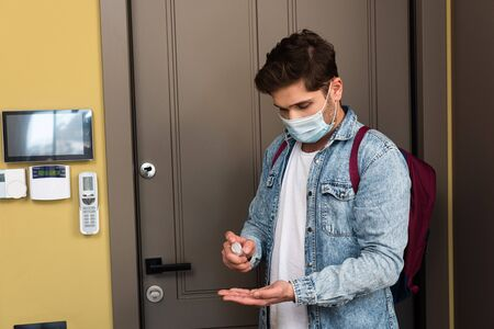 Young man in medical mask using hand sanitizer near door at home
