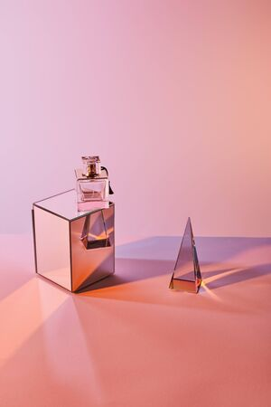 crystal transparent pyramid near perfume bottle on cube on pink background