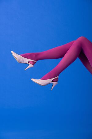 cropped view of model in purple tights and heels posing on blue