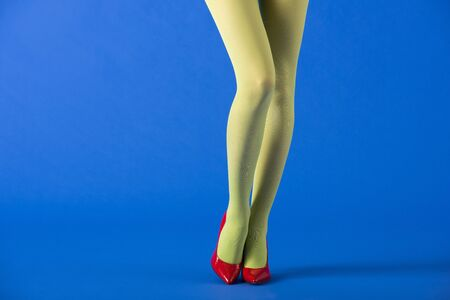 cropped view of model in green tights and red shoes standing on blue