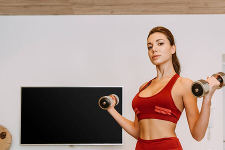 attractive woman training with dumbbells at home during self isolation
