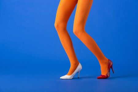cropped view of stylish model in orange tights, white and red heels posing on blue
