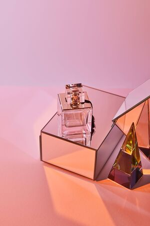 crystal transparent pyramid near perfume bottle and mirror cubes on pink background Stockfoto