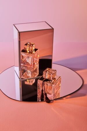 perfume bottle on round mirror with cube on pink background