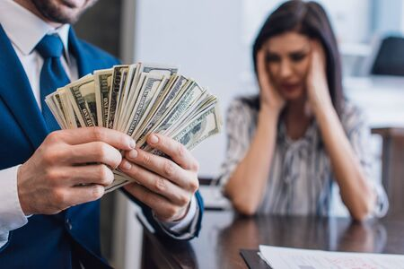 Selective focus of collector with money near stressed woman at table in room