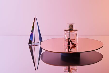 crystal transparent pyramid with reflection near perfume bottle on round mirror on pink background