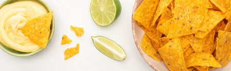 top view of corn nachos with lime and cheese sauce on white background, panoramic shot