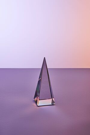 crystal transparent pyramid with light reflection on violet and purple background