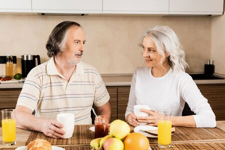 happy mature couple looking at each other near breakfast on table