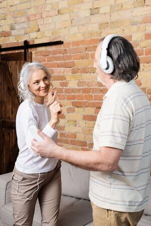 happy mature couple in wireless headphones dancing at home