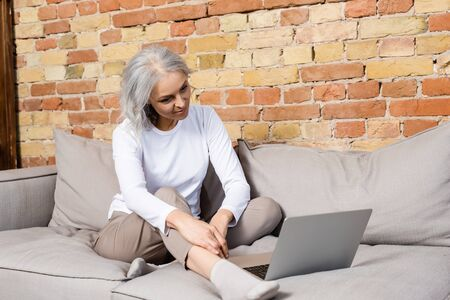 happy and mature woman watching movie on laptop in living room Banque d'images