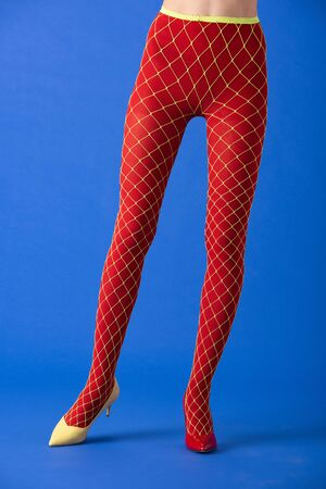 cropped view of model in fishnet tights, yellow and red heels standing on blue Stock Photo