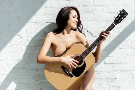 Beautiful naked woman smiling while playing acoustic guitar near white brick wall at home