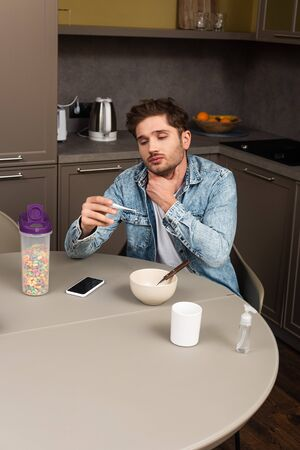 Diseased man touching neck and holding thermometer near smartphone and cereals on table in kitchen