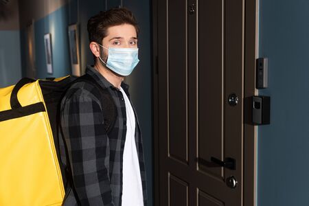 Side view of courier in medical mask with thermo backpack looking at camera near door in entryway