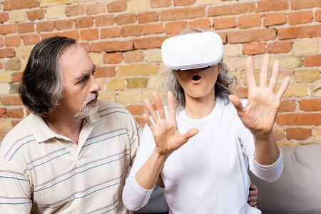 bearded and mature man looking at surprised wife in virtual reality headset gesturing at home 스톡 콘텐츠