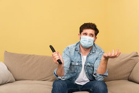 Confused man in medical mask holding remote controller at home