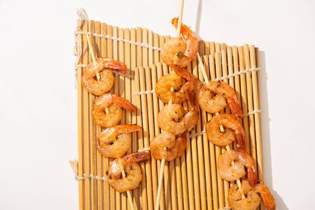 top view of prawns on skewers on bamboo mat on white background Фото со стока