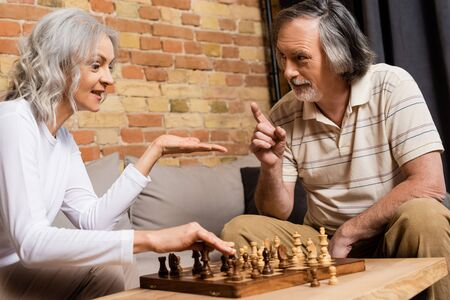 mature husband and wife playing chess in living room