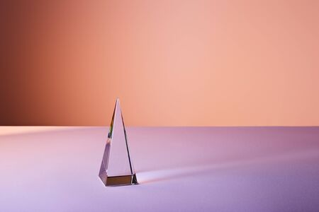 crystal transparent pyramid with light reflection on violet and orange background Stockfoto
