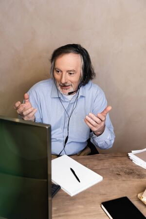 selective focus of middle aged operator in headset talking and gesturing while working from home