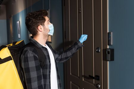 Side view of delivery man in medical mask and latex glove with thermo bag knocking in door