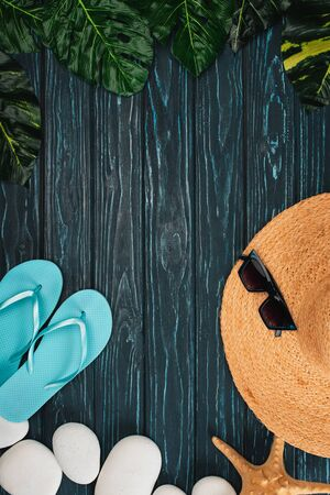 Top view of flip flops, straw hat near sunglasses and sea stones on dark wooden surface