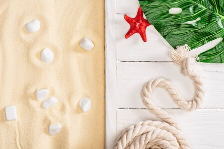 Top view of starfish, rope and green leaf on white wooden planks near pebbles on sand