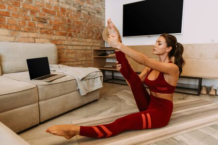 woman stretching online with laptop on yoga mat at home on self isolation 스톡 콘텐츠