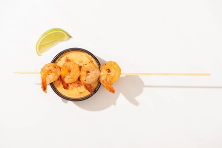 top view of delicious fried prawns on skewer with lime and sauce on white background
