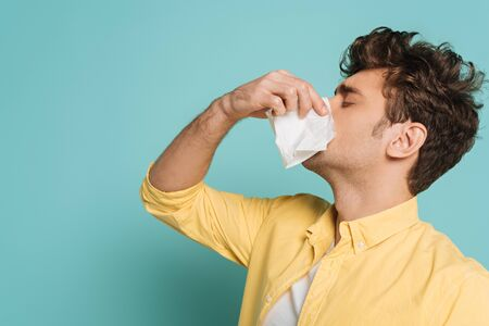 Man blowing out nose with napkins on blue