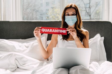 young freelancer in medical mask holding quarantine sign and working on laptop during self isolation in bed