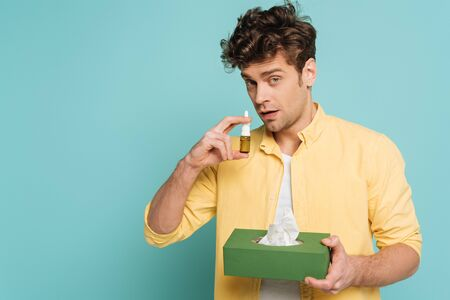 Man holding box with napkins, looking at camera and using nasal drops isolated on blue