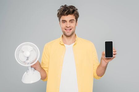 front view of man smiling, looking at camera and showing desk fan and smartphone 스톡 콘텐츠