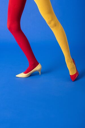 cropped view of woman in yellow and red tights and shoes posing on blue