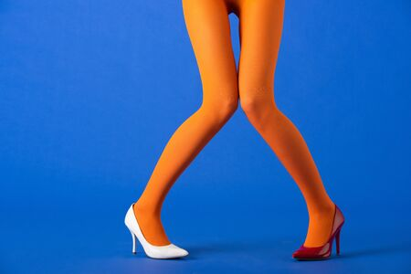 cropped view of woman in bright orange tights, white and red heels posing on blue