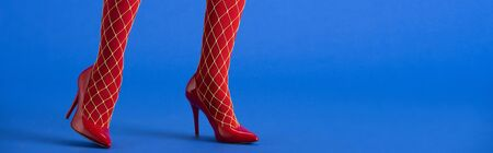 panoramic shot of woman in fishnet tights and red heels posing on blue