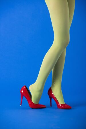 cropped view of stylish model in green tights and red heels standing on blue Stock Photo