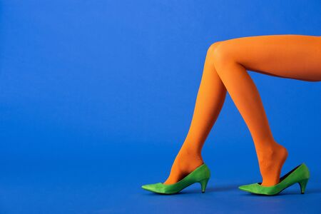 cropped view of woman in bright orange tights and green shoes sitting on blue