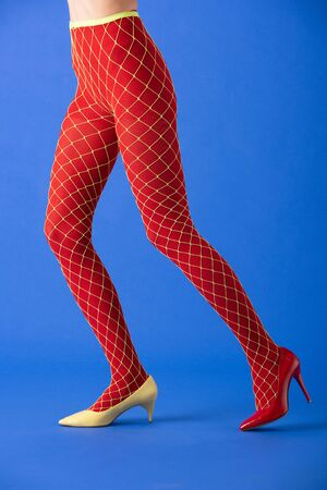 cropped view of woman in fishnet tights, yellow and red heels posing on blue