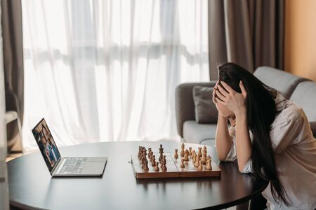 depressed woman touching bowed head while having video chat with boyfriend near chessboard