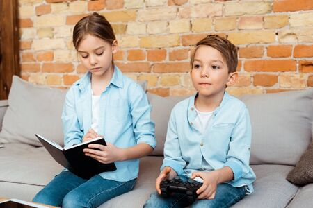 KYIV, UKRAINE - APRIL 27, 2020: sister writing in notebook near brother playing video game