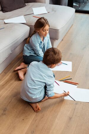 cute sister and brother sitting on floor and drawing in living room