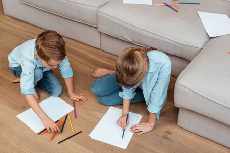sister and brother sitting on floor and drawing in living room Stockfoto