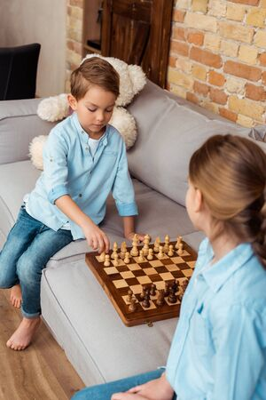 selective focus of siblings playing chess on sofa in living room