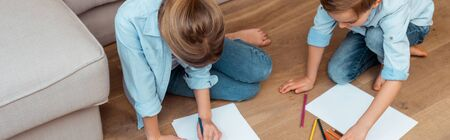 panoramic crop of sister and brother sitting on floor and drawing in living room