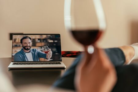 cropped view of woman and young man on screen of laptop toasting with glasses of red wine