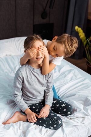cute brother covering eyes of sister in bedroom