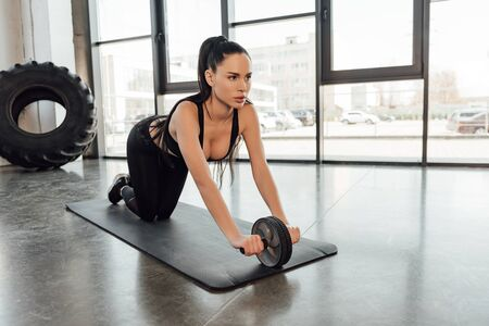 Attractive sportswoman training with adapter with barbell discs on fitness mat in gym